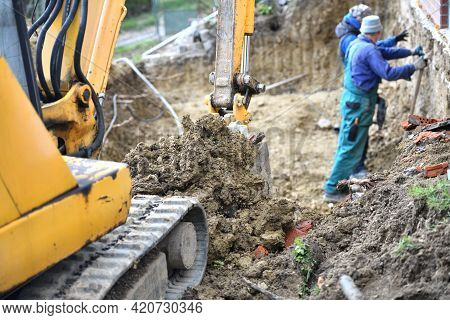A Combination Of Heavy Excavator Equipment And Human Masonry Work In Building A House
