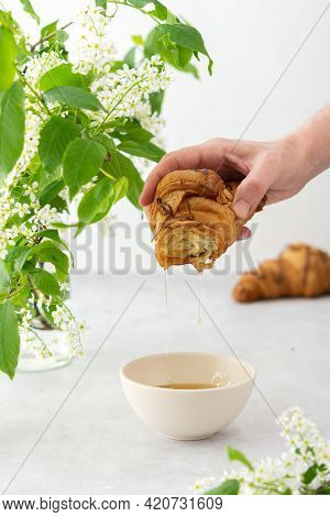 Breakfast With Coffee And Croissant, A Man's Hand Moistens A Croissant In Honey, Branches Of Bloomin
