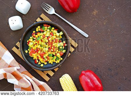 Vegetable Stew Or Warm Salad Made From Sweet Corn, Zucchini And Red Bell Pepper On A Clay Dish On A