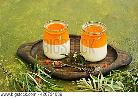 Dessert, Creamy Panna Cotta With Sea Buckthorn Jelly In Vintage Glass Jars On A Wooden Board Or Tray