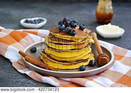Pumpkin Pancakes With Blueberries And Honey On A Brown Clay Plate On A Dark Concrete Background. Ame