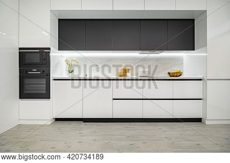 Luxury large modern white and black kitchen interior used as showcase, front view