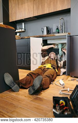 Young plumber lying on the floor while repairing kitchen sink