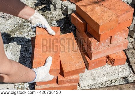 Construction work in a private house. A bricklayer takes bricks from a stack to build a wall.
