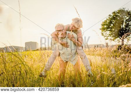 Strong senior man carrying his wife piggyback without back pain