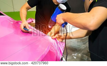 Master installs a tint film for the car glass with a hairdryer and spatula. Concept tinting car