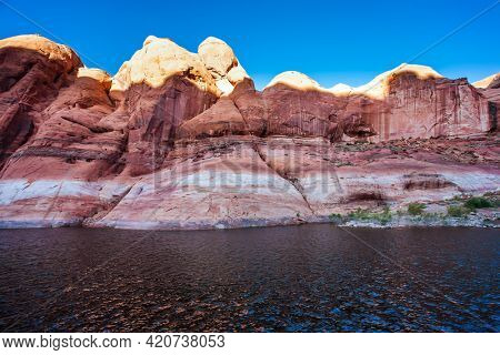 The Colorado River and Antelope Canyon. Grandiose cliffs - red sandstone outcroppings. Tour on a tourist boat on an artificial reservoir Lake Powell. Concept of active and photo tourism