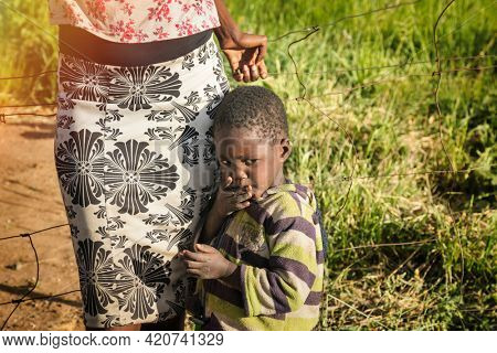 Portrait of a shy African boy  with his mom at sunset in his village in Botswana