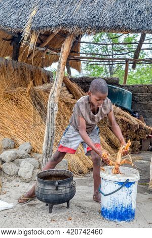 Portrait of an hungry African child boiling some roots in a pot in their kitchen yard in a village  in Botswana village