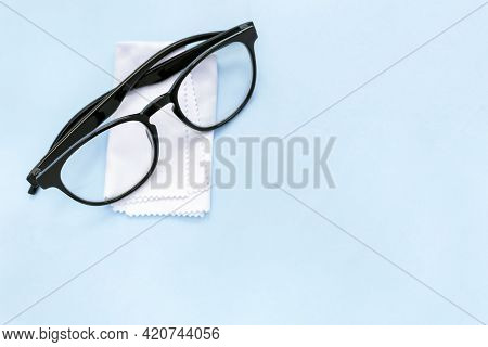 Black Rimmed Glasses And Cleaning Cloth On Blue Background With Copy Space. White Soft Tissue For Wi