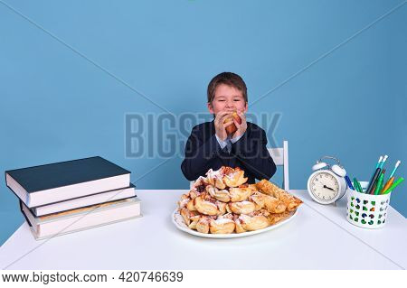 Funny Junior Boy Eating An Apple And A Plate Of Baked Buns On A Desk, Blue Background