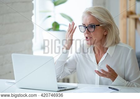 Angry Female Employee Frustrated By Laptop Problems
