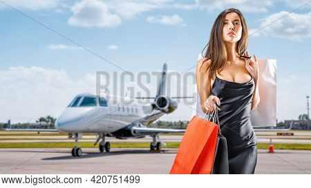 Young Lady With Shopping Bags Comes From A Private Jet