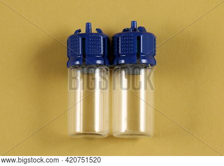 Empty Glass Vials For Medical Equipment Like Vaccine On Yellow Background