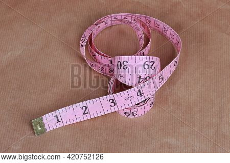 Pink Tailoring  Tape Measure Rolled On Paper Background
