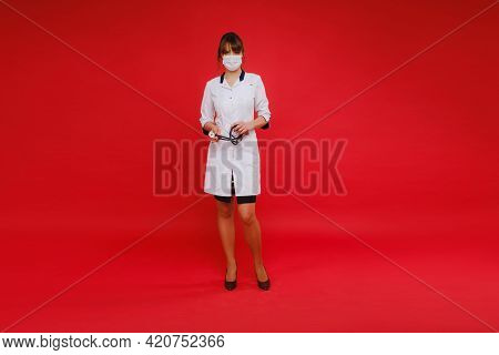 A Young Doctor In A White Coat And Medical Mask Stands On A Red Background