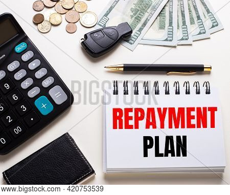 On A White Table Is A Calculator, Car Key, Cash, A Pen And A Notebook With The Inscription Repayment