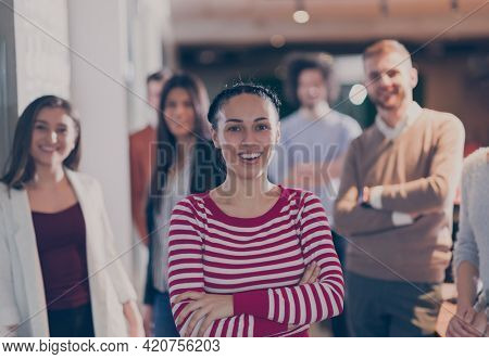 Beautiful Hispanic or modern Muslim businesswoman looking at camera and smiling coworkers diverse team in modern open space office in background