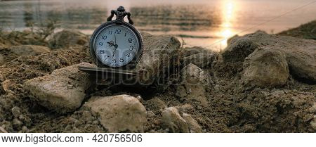 Closeup Of Classic Vintage Pocket Watch In Rear Of Beach, Rocks And Sunset Scenery. Landscape. Time.
