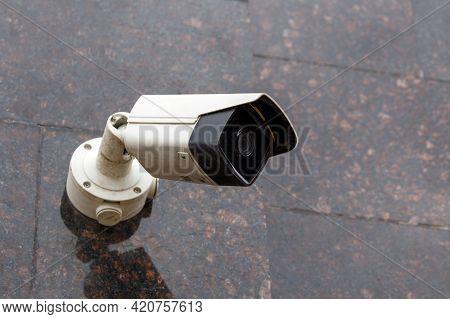 Small Cheap Surveillance Camera On Tan Brown Granite Wall