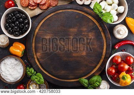 Pizza Ingredients On The Dark Background And Round Cutting Board, Free Space For Text. Pepperoni, Mo