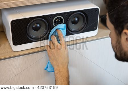 An Unrecognizable Caucasian Man Does A Wet Cleaning, Dusting A Musical Speaker System. Spring Cleani