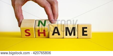 Name Or Shame Symbol. Businessman Turns Wooden Cubes And Changes The Word 'shame' To 'name' Or Vice