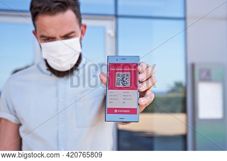 Man Holding Smartphone Displaying On App Mobile Expired Digital Vaccination Certificate For Covid-19