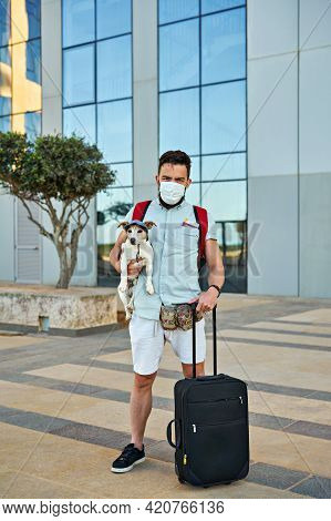 Tired Guy In Face Mask With Backpack, Suitcase And Dog In His Arms Is Going On Vacation. Travel With