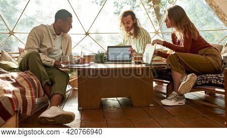 Team Of Young Multiracial Freelancers Discussing Project On Laptop While Working Together In Large T