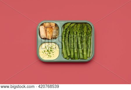 Above View With A Lunch Box Prepared With Baked Asparagus, Salmon Fish, And Hollandaise Sauce. Meal