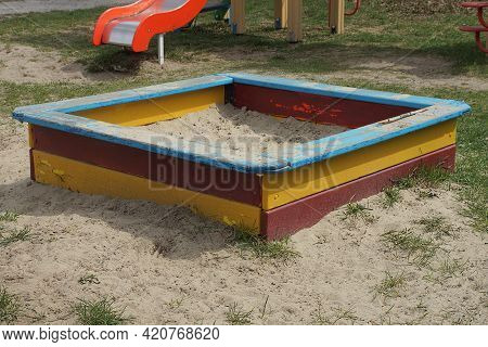 One Big Colored Square Wooden Sandbox With White Sand Stands On The Ground And Green Grass In The Pl