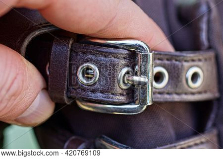 Fingers On His Hand Hold A Brown Harness Belt With A Gray Metal Buckle On The Bag