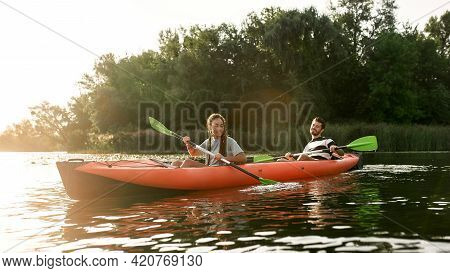 Adventurous Young Couple Kayaking In A River Surrounded By The Beautiful Nature On A Summer Day. Kay