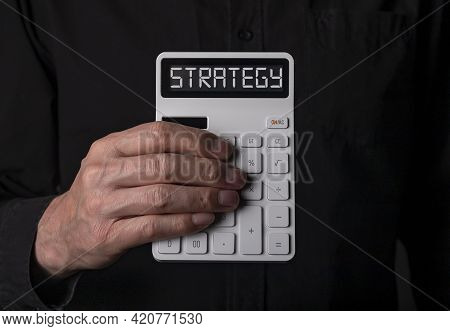 Financial Strategy Concept. Tax And Budget Planning And Vision. White Calculator Over Black Backgrou