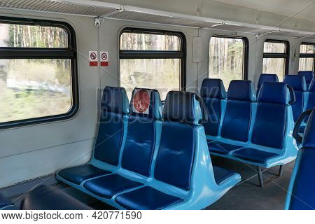 Empty Wagon In Train With Blue Chairs And Red Round Stickers With Restriction That Forbid To Take Up