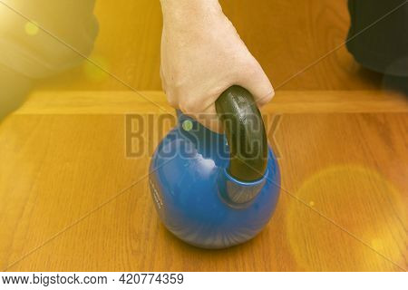 Iron Kettlebell In The Mans Hand On A Wooden Background. Close Up. Sports Kettlebell In The Gym, Top