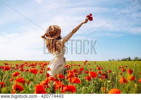 Romantic Woman With Flower In Hand Staying In Poppy Field. Relaxing On Summer Poppy Flowers Meadow.