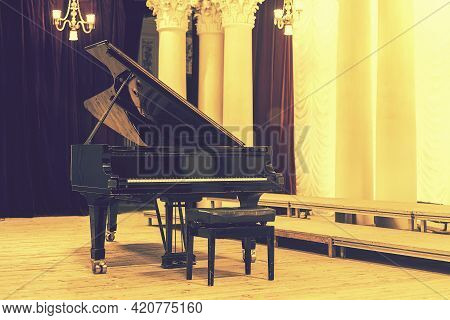 Grand Piano In Concert Hall. Piano Standing On Empty Stage. Opened Black Grand Piano With Stool On A