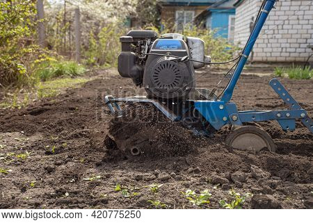 Cultivator Plows The Land, Loosen The Land With A Hand-held Motor Plow, Seasonal Gardening In Spring