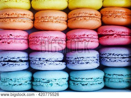 Multicolored  Rainbow Macaroon Desserts As Background. Delicious French Macaroons With Filling.