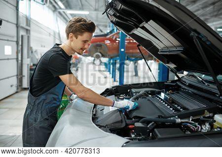 Male mechanic closes the hood, car service