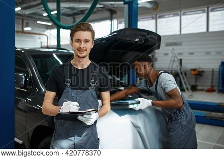 Two male workers repairs engine, car service
