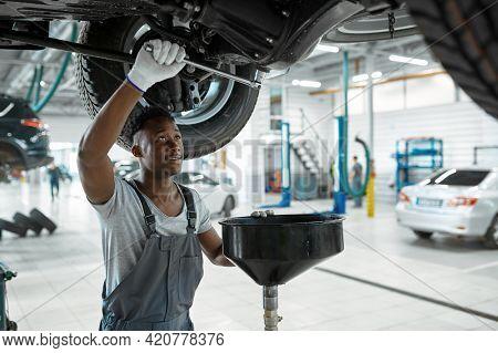 Male mechanic drains the oil, car service