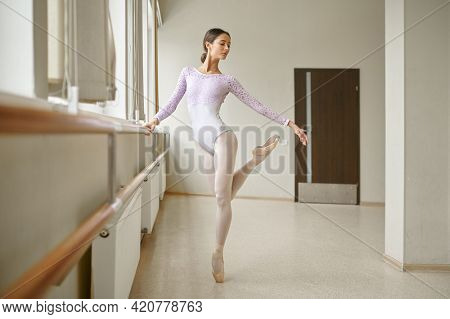 Ballerina in white clothes doing exercise at barre