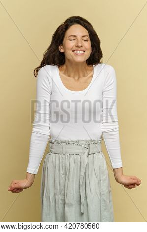 Happy Pleased Female In White Outfit Over Studio Wall Waiting For Surprise With Closed Eyes And Toot