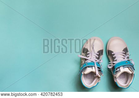 Baby Girl Sport Shoes On Blue Background. Kid Small Size Sneakers, Canvas Booties Closeup View. Spac