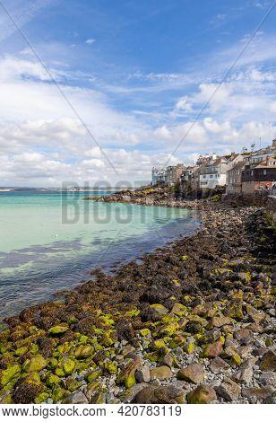 Rocky Cornwall coast with seaside buildings
