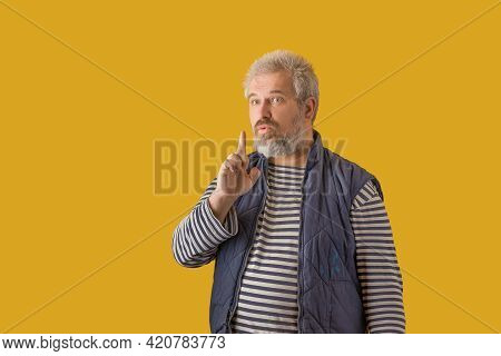 Man Shushing Face. On A Yellow Isolated Background.