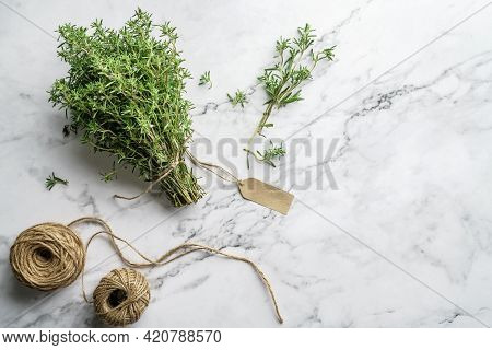 Thyme Herb Bunch. Bouquet Of Fresh Thymes On Light Marble Background With Skein Of Jute Twine. Top V